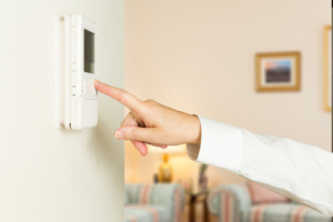 Woman pressing a modern thermostat - Air Conditioner Tempe AZ